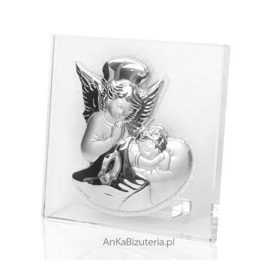 Srebrny obrazek Aniołek pochyljący się nad dzieciątkiem na szkle.