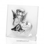 A silver picture of an angel leaning over a child on glass.