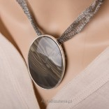 A large silver pendant with striped flint on a waving chain